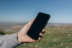 Schließen Sie oben von einem Mann unter Verwendung Telefons des im Freien lizenzfreie stockfotografie