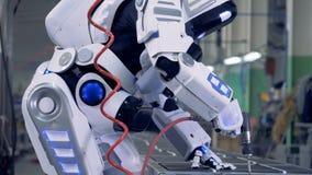 Schließen Sie oben von einem menschlich ähnlichen Roboter, der mit einem Bohrgerät arbeitet stock footage