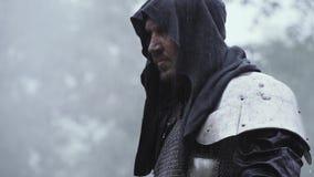 Schließen Sie oben von einem mittelalterlichen Krieger in der Metallrüstung und in einer Haube auf seinem Kopf stock video
