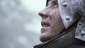 Schließen Sie oben von einem mittelalterlichen Soldaten mit Sturzhelm auf seinem Kopf, der oben schaut stock video footage