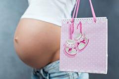 Schließen Sie oben von einem netten schwangeren anwesenden Paket des Bauches und des Geschenks Stockfoto