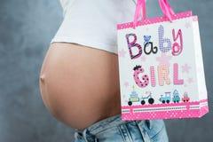 Schließen Sie oben von einem netten schwangeren anwesenden Paket des Bauches und des Geschenks Preg Stockfoto