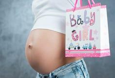 Schließen Sie oben von einem netten schwangeren anwesenden Paket des Bauches und des Geschenks Preg Stockfotografie