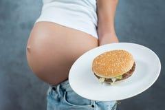 Schließen Sie oben von einem netten schwangeren Bauch und von einer ungesunden Fertigkost Lizenzfreies Stockbild