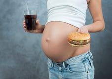 Schließen Sie oben von einem netten schwangeren Bauch und von einer ungesunden Fertigkost Lizenzfreie Stockfotografie