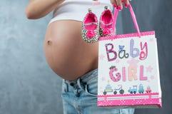 Schließen Sie oben von einem netten schwangeren Bauchbauch mit rosa Band Stockbild