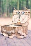 Schließen Sie oben von einem offenen Picknickkorb über Holztisch im Park Abbildung der roten Lilie Stockfotografie