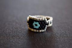 Schließen Sie oben von einem perlenbesetzten Ring auf einer schwarzen Oberfläche Lizenzfreie Stockfotografie