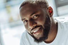 Schließen Sie oben von einem positiven afroen-amerikanisch Mannlächeln stockfotografie