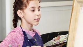 Schließen Sie oben von einem recht kleinen Mädchen, welches das pallette hält, das ein Bild malt stock video footage