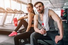 Schließen Sie oben von einem schönen Paar, das auf der Sportbank und -aufstellung sitzt Auch sie sind Trinkwasser von ihren Flasc lizenzfreies stockbild