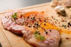 Schließen Sie oben von einem Steak des rohen Fleisches mit Gewürzen Lizenzfreie Stockbilder