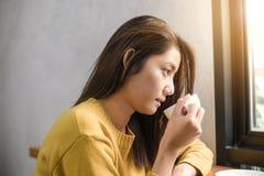 Schließen Sie oben von einem trinkenden Kaffee der jungen Asiatin in der Kaffeestube, die einen Tasse Kaffee in ihrer Hand hält stockfoto
