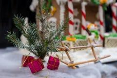 Schließen Sie oben von einem Zweig des Weihnachtsbaums mit kleine Geschenke nahem Ging Lizenzfreie Stockfotografie