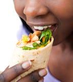 Schließen Sie oben von einer afrikanischen Frau, die einen Burrito verschlingt Stockfotos