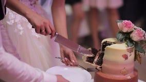 Schließen Sie oben von einer Braut und von einem Bräutigam, die ihre Hochzeitstorte schneiden stock video