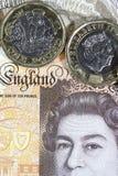 Schließen Sie oben von einer ein Pfund-Münze mit einem zehn Pfund-Anmerkungshintergrund - britische Währung Stockbild