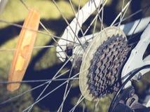 Schließen Sie oben von einer Fahrradfelge mit Detail-, Ketten- und Schalthebelmechanismus, im Morgensonnenlicht Lizenzfreie Stockfotografie