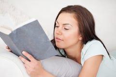 Schließen Sie oben von einer Frau auf einem Sofa ein Buch lesend Stockbilder