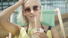 Schließen Sie oben von einer Frau, die ein tropisches mojito Cocktail trinkt, das mit frischer Frucht durch ein Stroh auf ihren S Stockfotografie