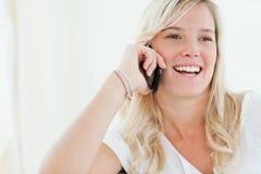 Schließen Sie oben von einer Frau, die an ihrem Telefon lacht, wie sie zum si schaut Lizenzfreies Stockfoto