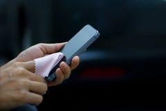Schließen Sie oben von einer Frau, die intelligentes Mobiltelefon mit Gewebe im dunklen Hintergrund säubert Stockbilder