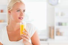 Schließen Sie oben von einer Frau, die Orangensaft trinkt Lizenzfreies Stockbild