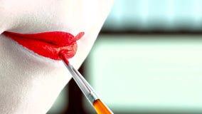 Schließen Sie oben von einer Frau mit klassischem Japaner bilden auf ihren Lippen Geisha mit den roten Lippen stockbild