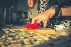 Schließen Sie oben von einer Frauenhand, die einen Paprika schneidet stockfotos