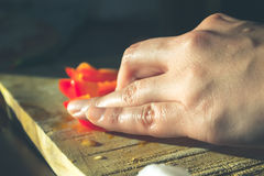 Schließen Sie oben von einer Frauenhand, die einen Paprika schneidet lizenzfreie stockfotografie