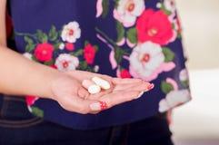 Schließen Sie oben von einer Frauenhand und in ihrer offenen Hand eine vaginale Tablette oder ein Zäpfchen der weichen Gelatine h Stockbild