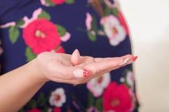 Schließen Sie oben von einer Frauenhand und in ihrer offenen Hand eine vaginale Tablette oder ein Zäpfchen der weichen Gelatine h Lizenzfreies Stockfoto