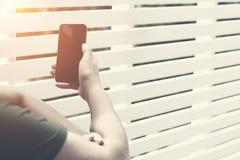 Schließen Sie oben von einer Frauenhand unter Verwendung ihres Handys auf der Reise b stockfotos