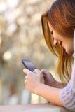 Schließen Sie oben von einer glücklichen Frau, die ein intelligentes Telefon verwendet Lizenzfreie Stockbilder