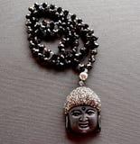 Schließen Sie oben von einer Halskette, die von den schwarzen Kristallen und von Buddha-Kopf gemacht wird stockfotos