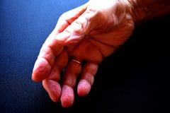 Schließen Sie oben von einer Hand der alten Frau auf einer schwarzen Tabelle Lizenzfreies Stockbild