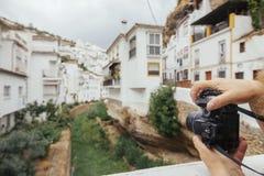 Schließen Sie oben von einer Hand einer Frau, die Fotos auf einem malerischen Dorf macht Stockfotos
