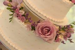 Schließen Sie oben von einer Hochzeitstorte, mit Blumen Lizenzfreie Stockfotos