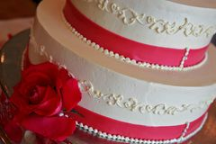 Schließen Sie oben von einer Hochzeitstorte mit einer Rose Stockfoto
