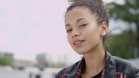 Schließen Sie oben von einer jungen Afroamerikanerfrau, die zu einer Kamera lächelt stock footage