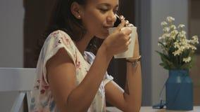 Schließen Sie oben von einer jungen afroen-amerikanisch Frau, die auf Handy und trinkender heißer Schokolade beim Sitzen in einer stock video footage