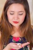 Schließen Sie oben von einer jungen Frau, die in ihrer Hand eine vaginale Tablette der weichen Gelatine oder ein Zäpfchen, Behand Stockbild