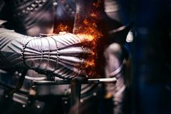Schließen Sie oben von einer mittelalterlichen Stahlrüstung mit der Eisenhandschuhhand, die mit Flammen des Feuers birst lizenzfreie stockbilder