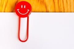 Schließen Sie oben von einer roten Büroklammer und von einem Weißbuch lizenzfreies stockbild