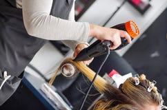 Schließen Sie oben von einer Schönheit in einem Friseursalon und vom Friseur, der blondes Haar mit Haartrockner und Rundbürste in Lizenzfreie Stockfotografie