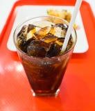 Schließen Sie oben von einer Schale des alkoholfreien Getränkes auf dem roten Behälter mit undeutlichem Lebensmitteltellerhinterg Stockfotografie