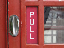 Schließen Sie oben von einer traditionellen roten britischen Telefonzelletür Lizenzfreie Stockfotos