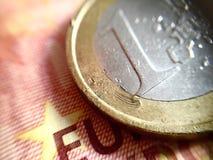 Schließen Sie oben von einer verkratzten '1â ¬ Münze über einer '10â ¬ Banknote Lizenzfreie Stockbilder