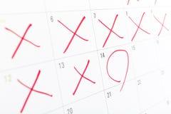 Schließen Sie oben von einer weißen Kalenderseite mit einigem die Tage, die weg von rotem X gekreuzt werden Lizenzfreie Stockfotos