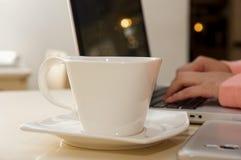 Schließen Sie oben von einer weißen Schale coffe mit einer unscharfen Geschäftsfrauhand, die im Hintergrund arbeitet Die goldene  Lizenzfreie Stockfotos